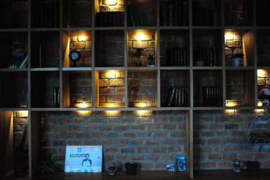 The shelf display looks like one you would find at Caffe Bene, but it is filled with books by and about Kim Il Sung. In the bottom left you can see the barista's certificate – she trained at a barista academy in China. Image by Alek Sigley.