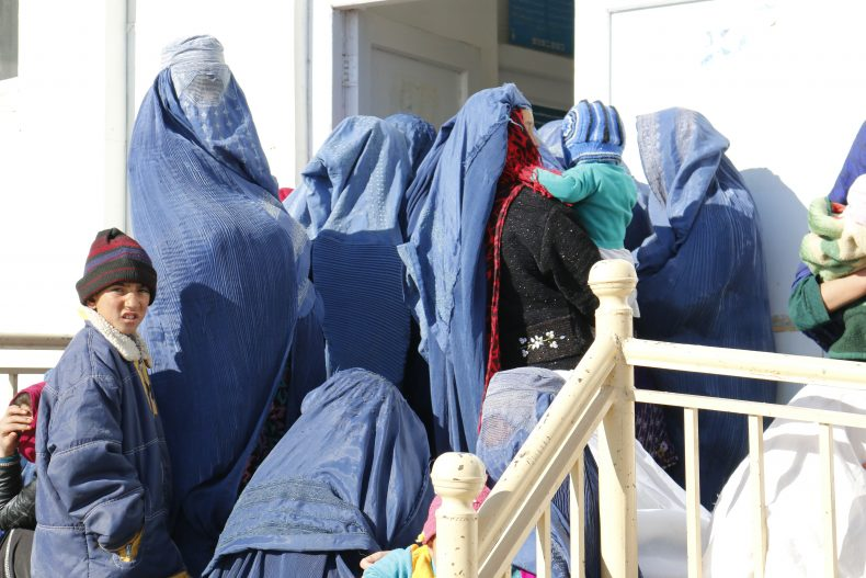 Afghan women wait outside a Basic Package of Health Services (BPHS) Clinic to seek maternal health advise where the midwife would also notice the bruises on their body parts. Image by Ritu Mahendru.