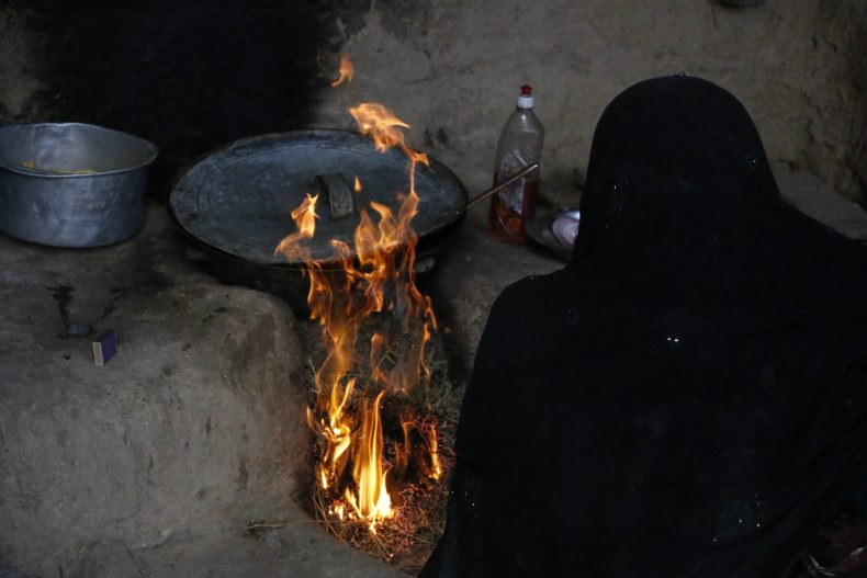 A 16 year old Afghan girl married at the age of 13 cooks for her family in an Afghan village. Image by Ritu Mahendru.