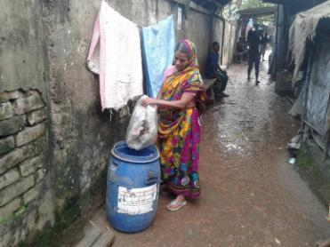 An inhabitant of Medical community putting her household garbage into a drum. Photo Credit: Sakib Imtiaz
