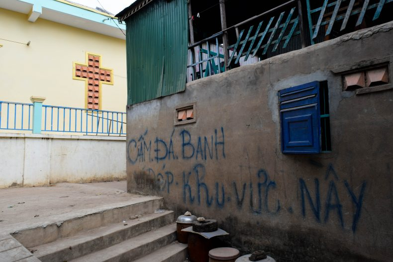 The writing on the wall, in Vietnamese, announces that the play of football is banned near the church and school. Image by Peter Ford.