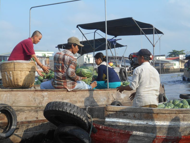 People exchange goods from boat to boat at one of the floating markets in the Mekong Delta. Image by Dao Ngoc Canh.