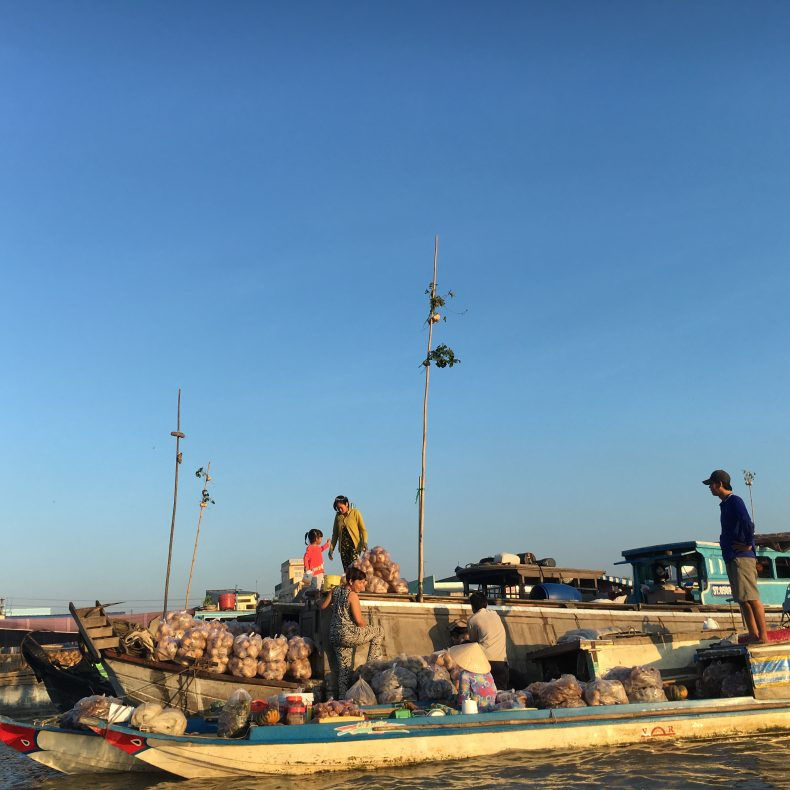 A family aboard one of the floating market's many boats. Image by Dao Ngoc Canh.